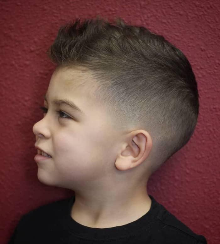 Das kleine Kind mit welligem Haar und Hinterschnitt